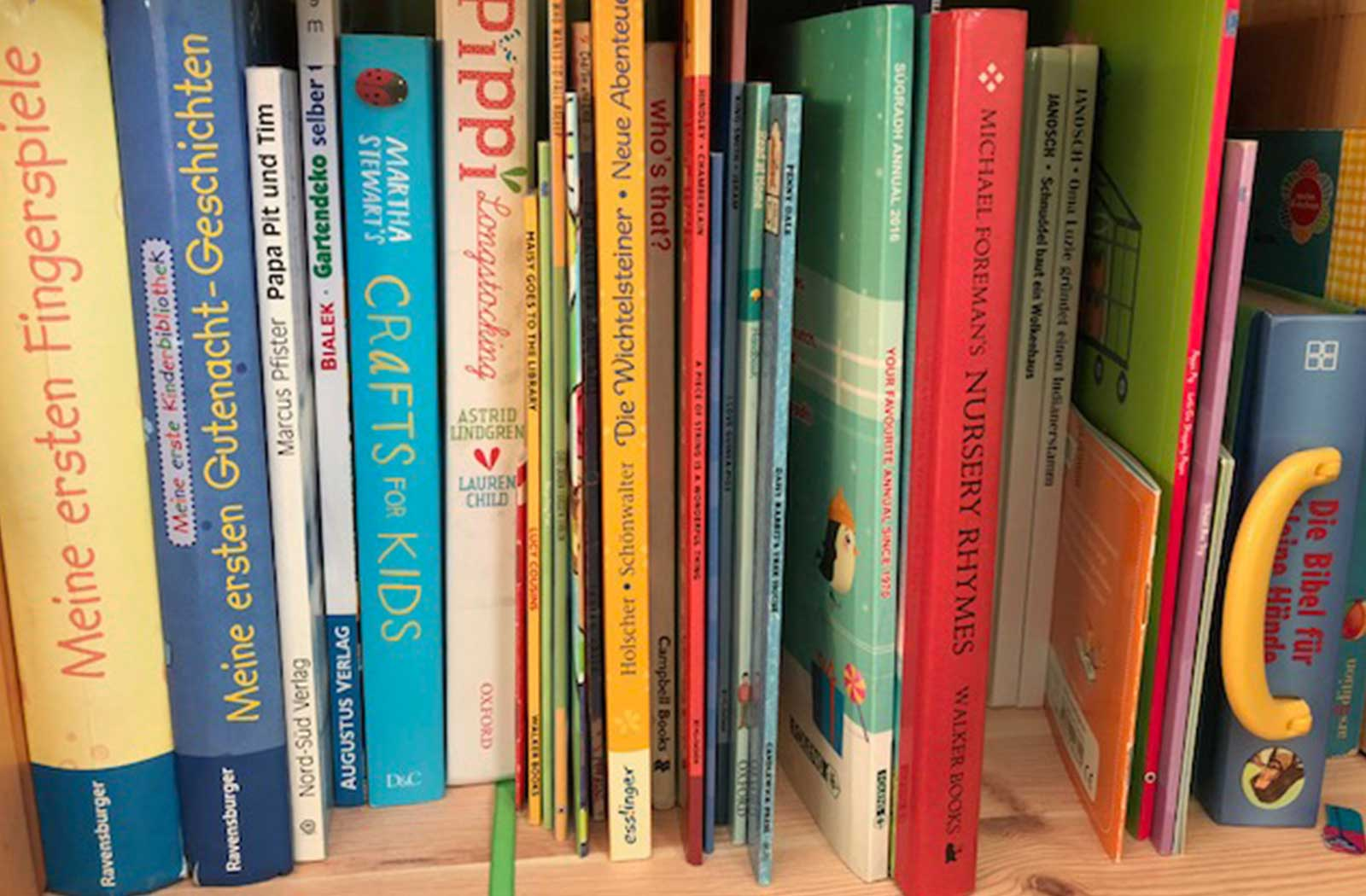 A very full bookshelf with books in various languages, offering children opportunities